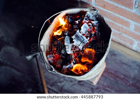 A bucket of burning coals from the stove against the wooden floor and brick walls. - stock photo