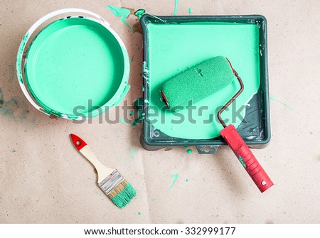 a bucket of paint and a brush roller paint tray - stock photo