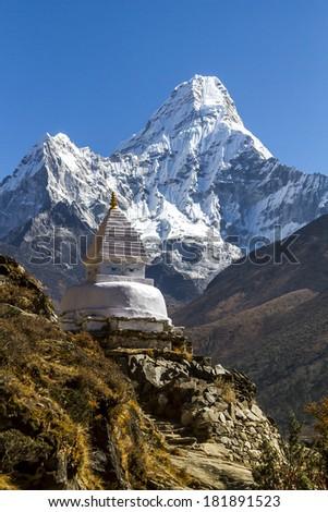 a Buddhist stupa and a Himalayan mountain - stock photo