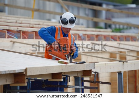 A builder uses a nail gun to secure timber on the verandah of new building - stock photo