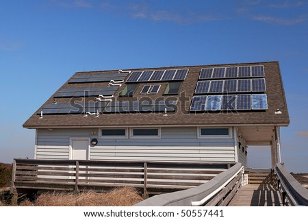 A building at the seashore uses solar water heating and electricity for its energy needs. - stock photo
