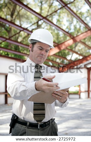 A building inspector on site reviewing his notes.  Vertical view. - stock photo