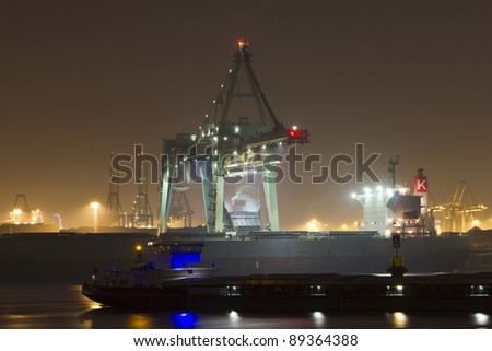 A bulk-carrier supplying cargo (coal) and an inland canal vessel (foreground) in the port of Rotterdam - stock photo