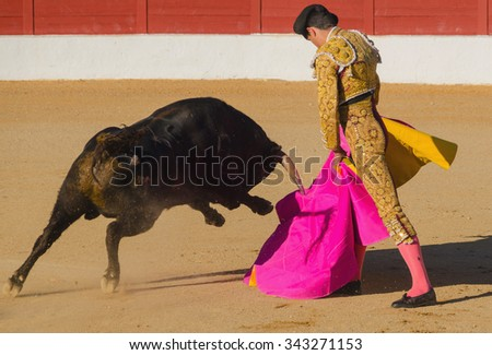 A bullfighter giving a pass to the bull with his cape. The matador confronts the bull with the capote - stock photo