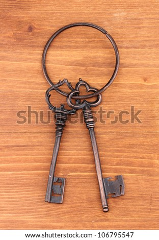 a bunch of antique keys on wooden background - stock photo