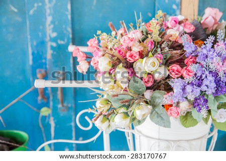 A bunch of beautiful artificial flowers in a vase - stock photo