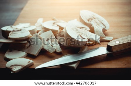 A bunch of cut mushrooms champignon on a wooden board and knife. - stock photo