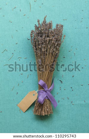 A bunch of dried lavender with blank card on blue linen canvas background - stock photo