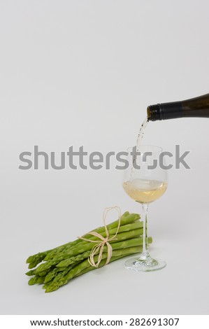 A bunch of fresh green Asparagus on white, with a glass of White Wine. Wine is poured into the glass. - stock photo