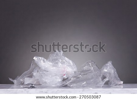 A bunch of plastic garbage lies on a marble table. Gray Background.  - stock photo