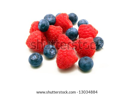 A bunch of plump delicious raspberries and blueberries isolated on white - stock photo