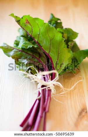 a bunch of red chard leaves on wooden  table - stock photo