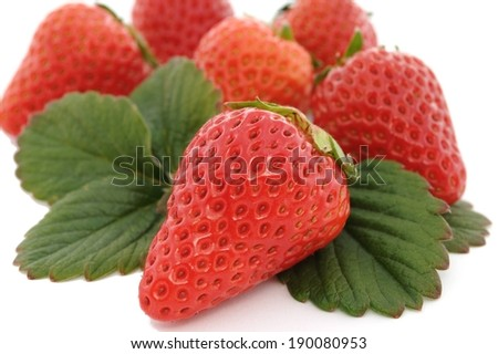 A bunch of ripe strawberries and leaves in a pile. - stock photo