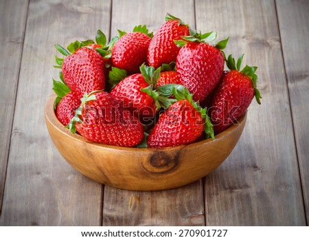 a bunch of ripe strawberries in a wooden bowl on the table - stock photo
