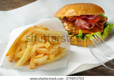 A burger, fries and fork with knife on paper - stock photo