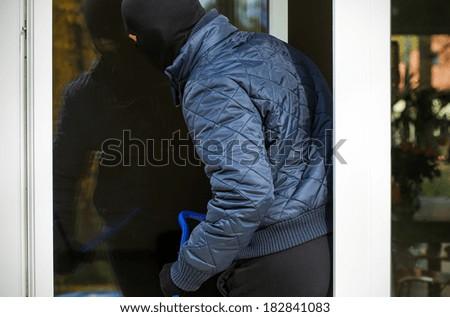 A burglar entering a house through an open window - stock photo