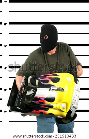 A Burglar in a Black Ski Mask, with Black Gloves is booked by the Police and his Mug Shot aka MUGSHOT taken. Bad Guys who get caught get mug shots. Holding his stolen property in the photo. Bad man - stock photo