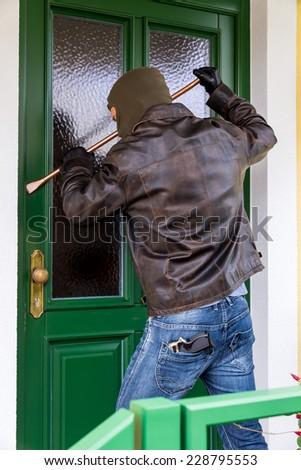 a burglar trying to break a door. - stock photo