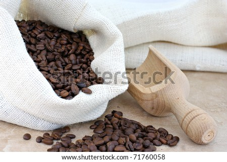 A burlap sack of fresh coffee beans with a wooden scoop to the side. - stock photo