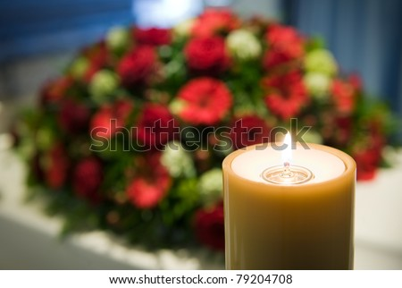 A burning candle with a white coffin and a flower-arrangement on the background in a mortuary - stock photo