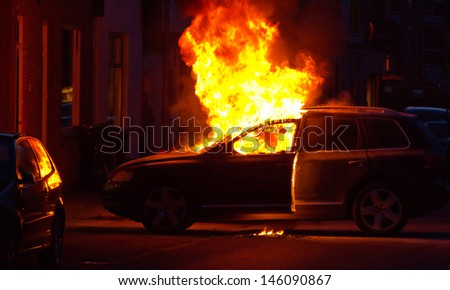 A burning car in a street - stock photo