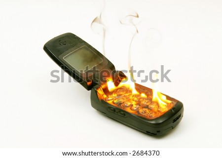 A burning cellphone against a white background, as an abstract for burning up call time, or eliminating the phone in revenge for its cost. - stock photo