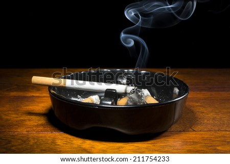 A burning cigar in a classic black ashtray streaming smoking in a dark, moody setting.  The smoke is real, straight from the cigarette and not put in later during post processing. - stock photo