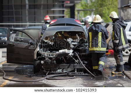 A burnt car and fire fighters around it - stock photo