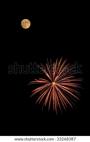 A burst of red and yellow fireworks in close proximity to the full moon. - stock photo