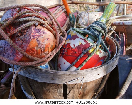 A bushel of colorful old crab pot buoys and boat ropes outside in the sunlight. - stock photo