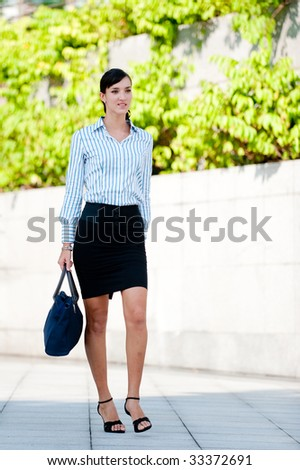 A business executive walking in a green part of the city - stock photo