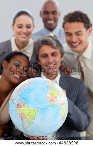 A business group showing ethnic diversity holding a terretrial gobe in the office - stock photo
