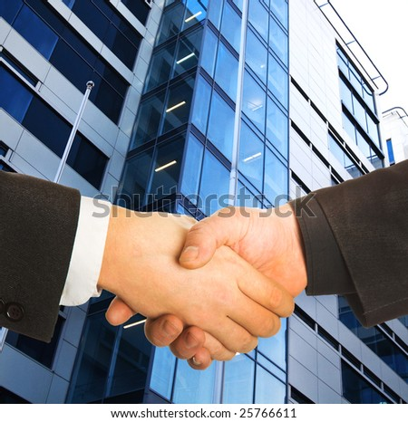 A business handshake in front of a building. - stock photo