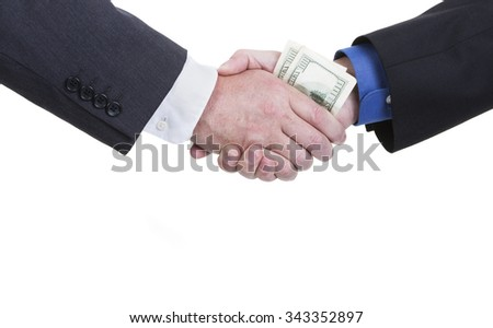 A business handshake with money being exchanged on a white background with copy space. - stock photo