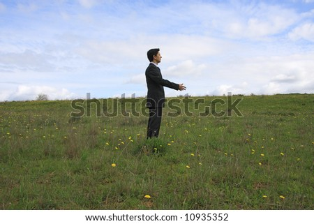 A business man alone on a field shaking hand with an invisible person - stock photo