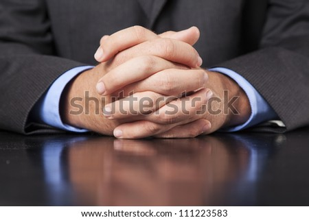 A business man dressed in a suit sits at a desk and clasps his hands firmly. - stock photo