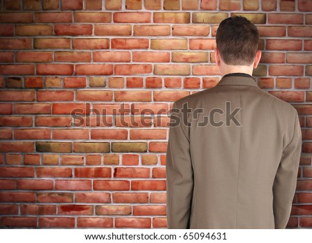 A business man has his back turned and looking at a brick wall. Can represent an obstacle, sadness or a struggle. - stock photo