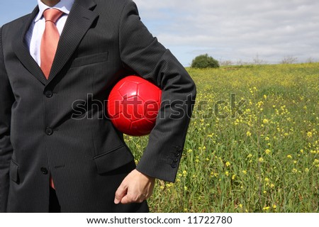 A business man holding a ball on a field - stock photo