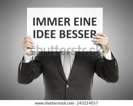 A business man holding a paper in front of his face with the message always one  step ahead in german language - stock photo