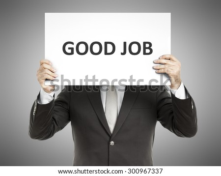 A business man holding a paper in front of his face with the message good job - stock photo