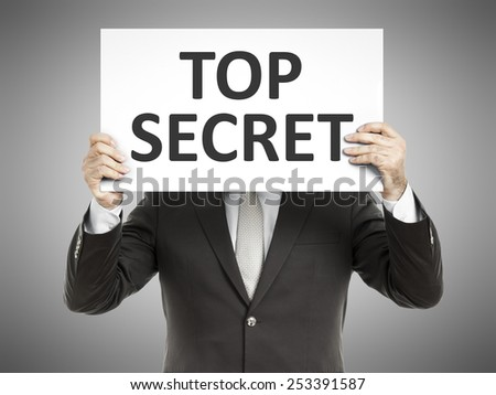 A business man holding a paper in front of his face with the message top secret - stock photo