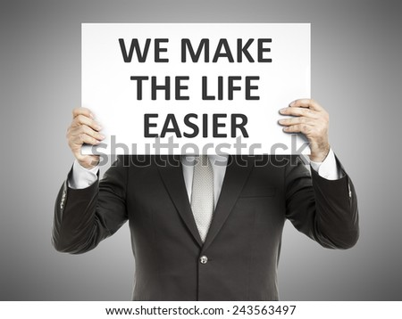 A business man holding a paper in front of his face with the message we make the life easier - stock photo