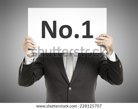 A business man holding a paper in front of his face with the text number one - stock photo