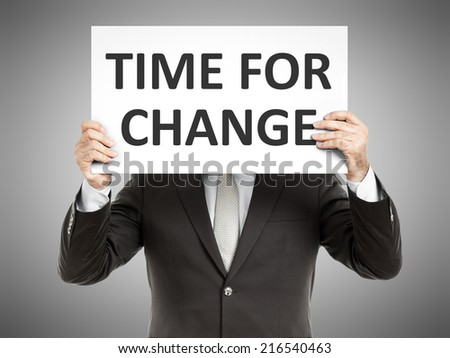 A business man holding a paper in front of his face with the text time for change - stock photo