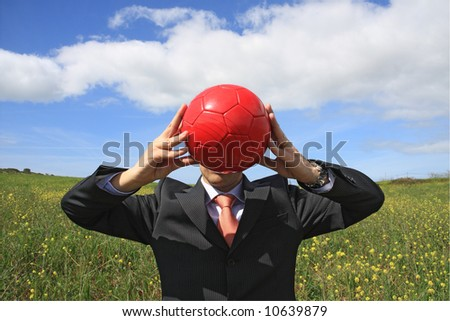 A business man holding a red ball hiding his face - stock photo