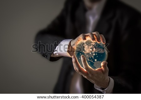 A business man in a suit holding a glowing orb of earth with some illuminated spots. - stock photo