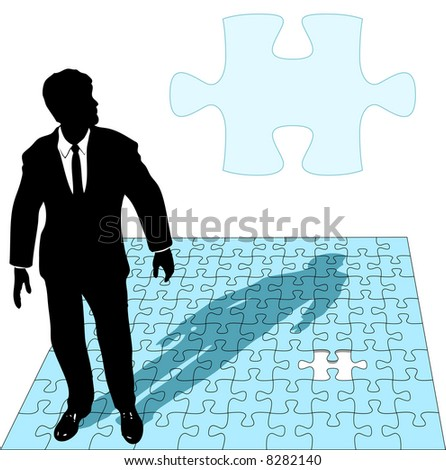 A business man in a suit works the last missing piece of a jigsaw puzzle solution, as copyspace. - stock photo