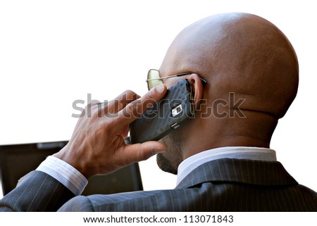 A business man in his early 30s talking on his smart phone and working on his laptop or netbook computer. - stock photo