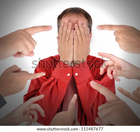 A business man is covering his eyes with his hands and has blame and shame with fingers pointing at him. - stock photo