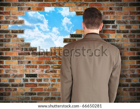 A business man is facing a brick wall with a hole of clouds in it representing escape. Use it for a freedom or barrier concept. - stock photo
